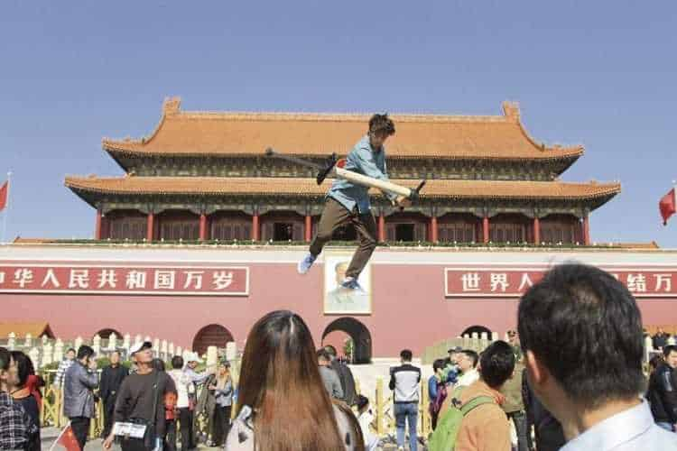 man jumping on pogo stick high above crowd in china square