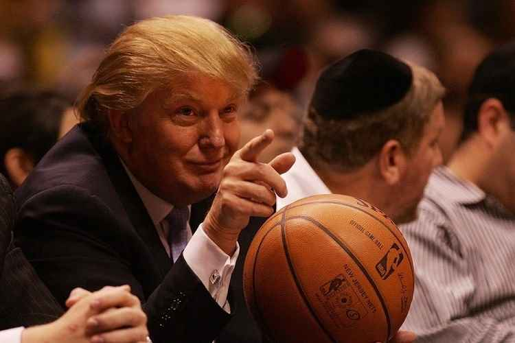 us president donald trump holding a basketball and pointing