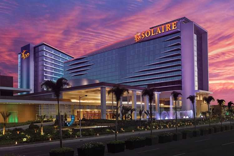 solaire casino in the philippines at sunset with a pink and orange sky